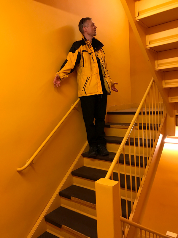 Stairwell with black steps and a yellow wall, me in black pants and a yellow and black jacket.