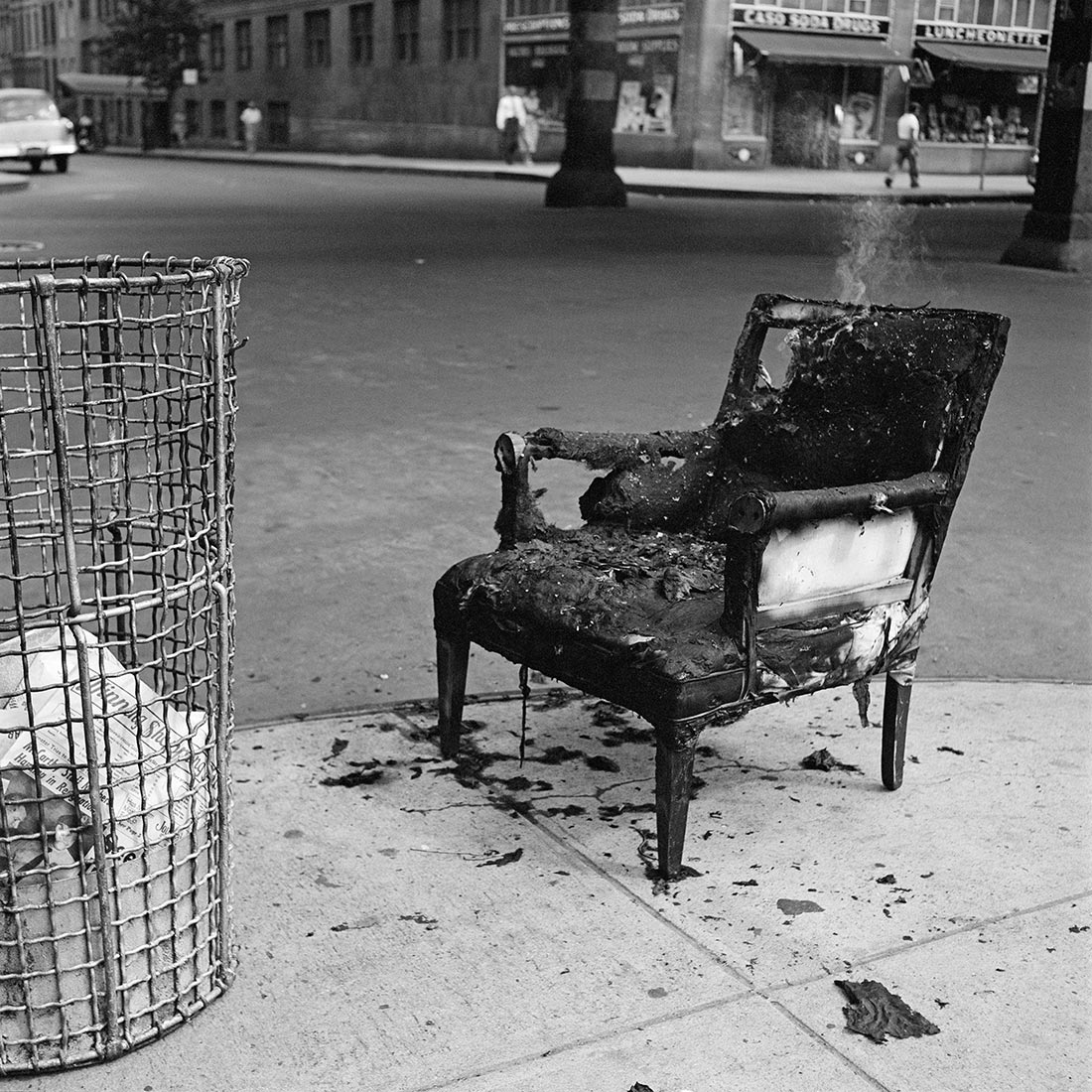 A burnt chair on a street corner with a wisp of smoke rising from it