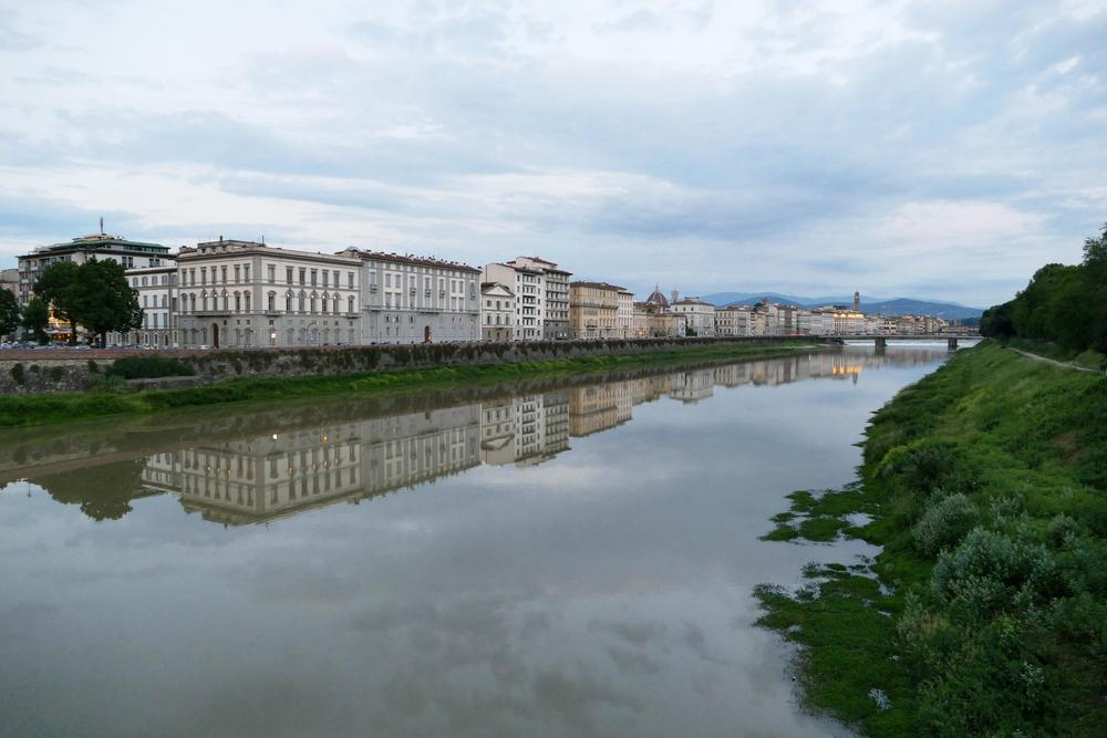 Buildings reflected in the Arno River.