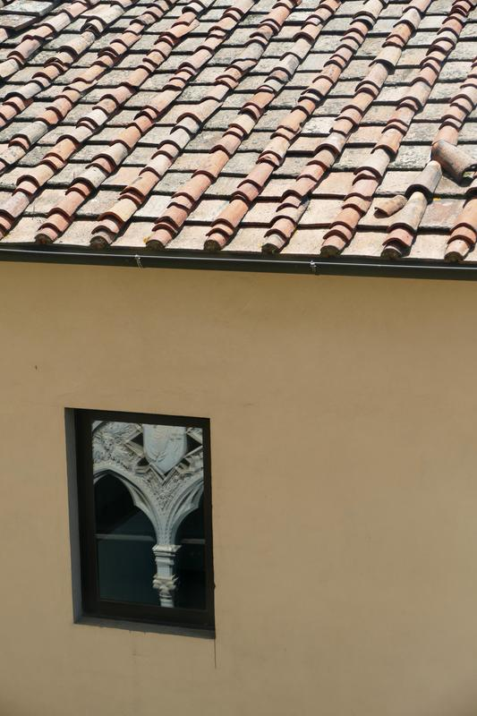 Tile roof and window, with church ornamentation reflected in the window.