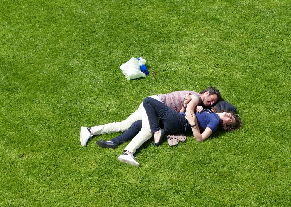 A couple lying together on the grass.