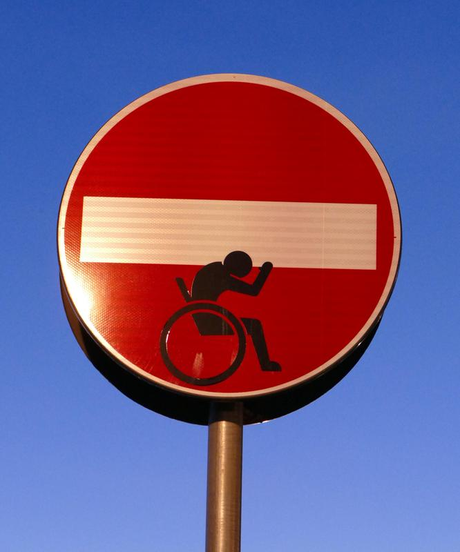 "A ""no entry"" street sign modified to show someone in a wheelchair attempting to support the white no-entry bar"