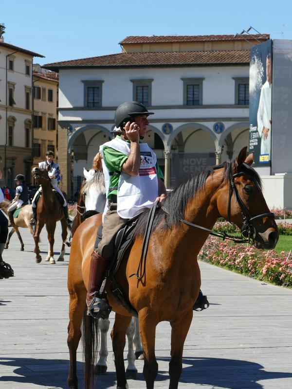 Man in Santa Maria Novella Piazza on a horse ... on a cellphone.