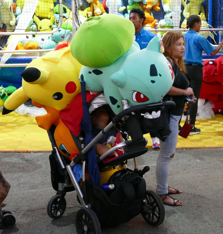 Three huge Pokemon overshadow a sleeping child in a stroller.