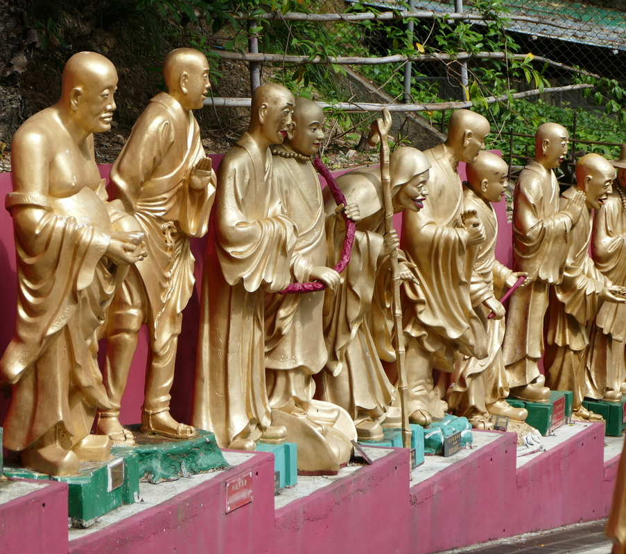life-size, gold-plated monks lining the path to the temple