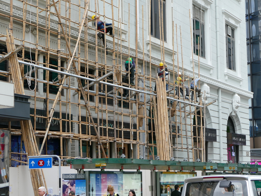 Men crawling up the second and third storey of bamboo scaffolding