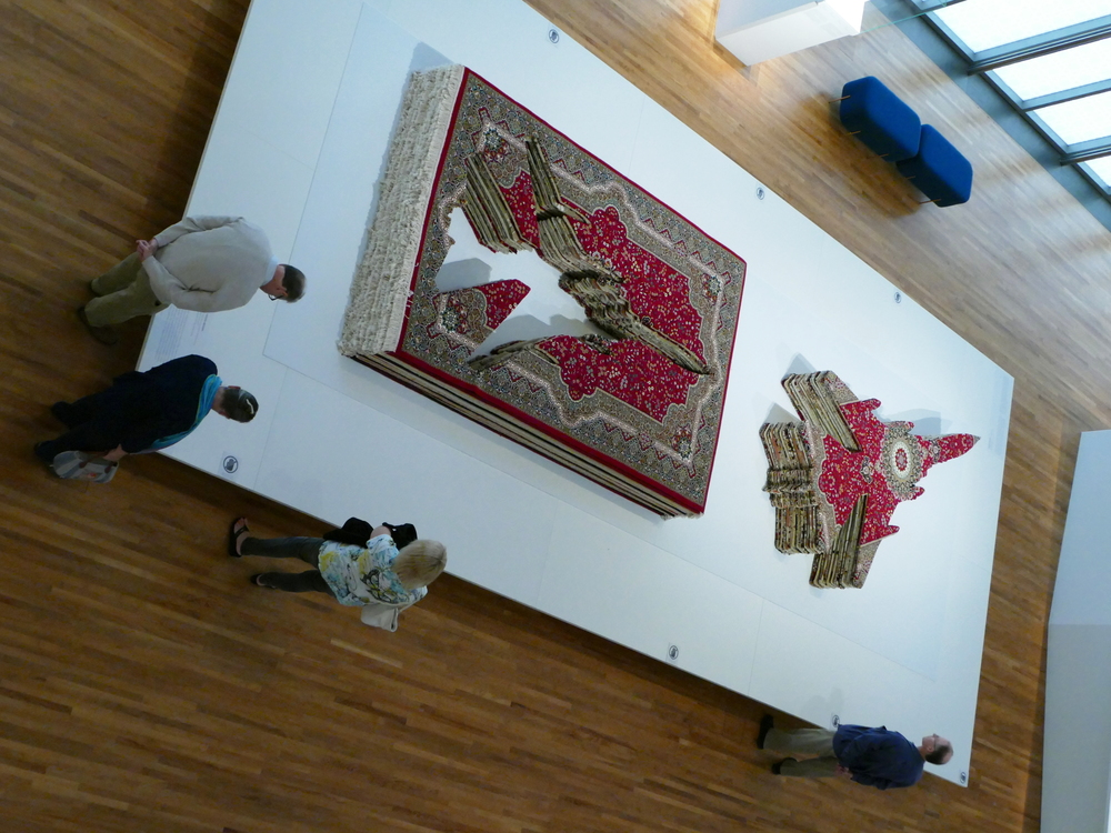 A stack of Persian carpets with the shape of a war plane cut out of them