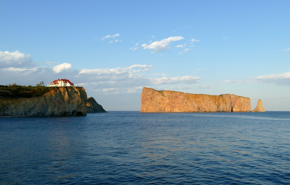A house on a cliff and the huge Percé Rock with a hole through it