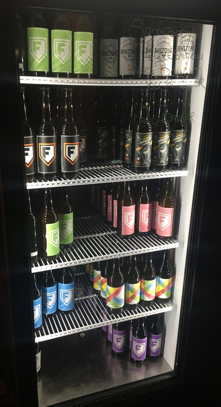 A selection of bottles for sale in the fridge at the front of the bar