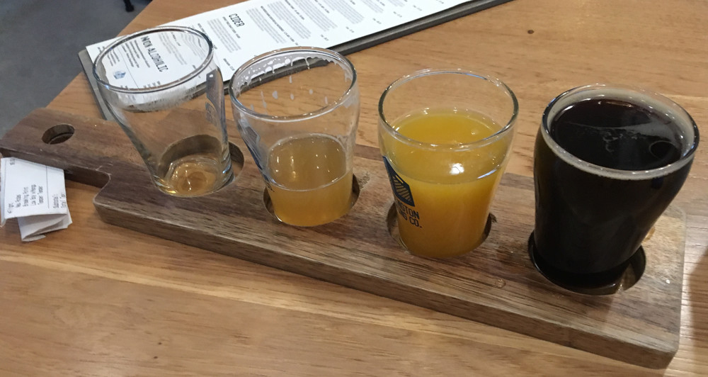 four small beers, one empty, the double IPA nearly empty, one bright orange, and one very dark