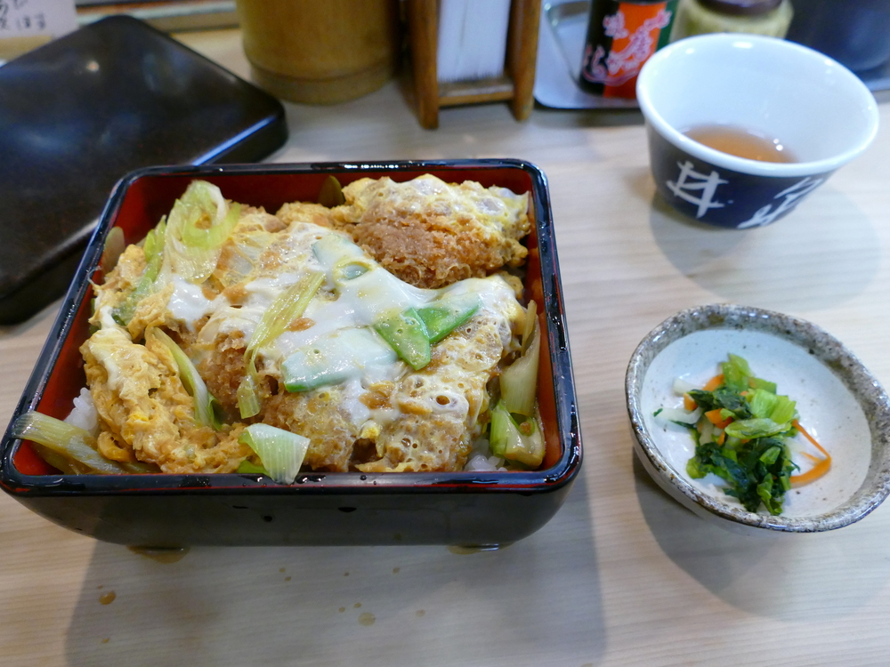 breaded, deep fried pork cutlet with egg on rice, small pickled vegetables on the side