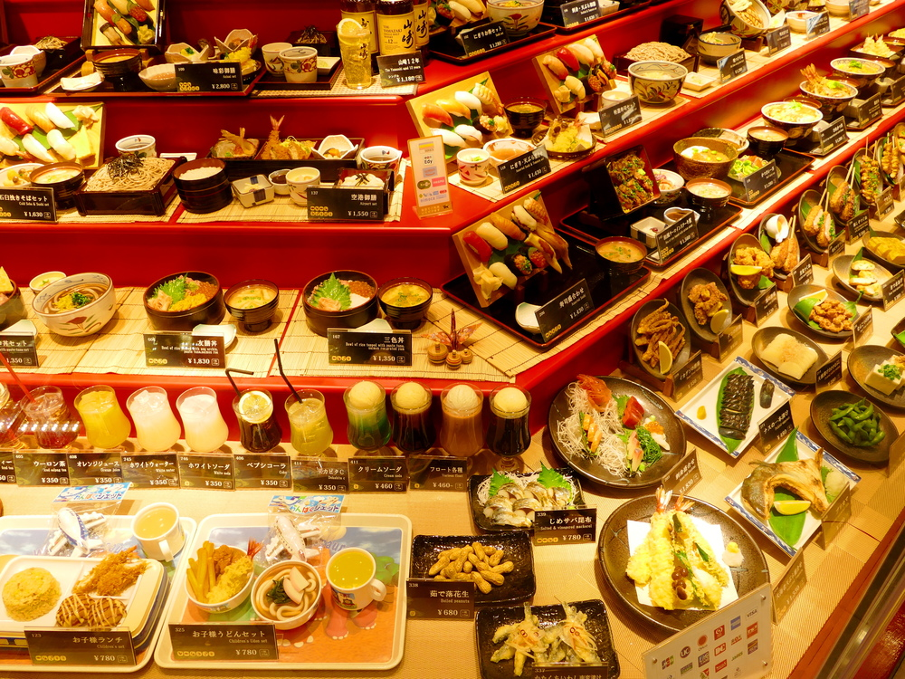 Multiple Japanese meals displayed incredibly convincingly in plastic, advertising a restaurant