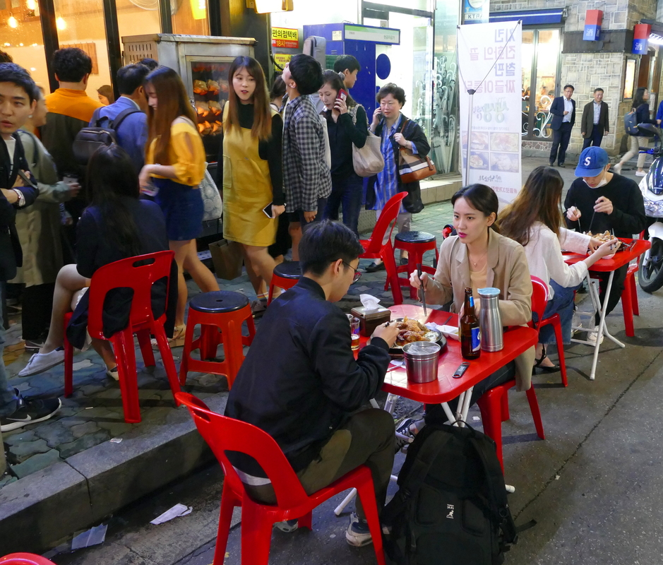 people on red plastic stools at small tables, eating on the street