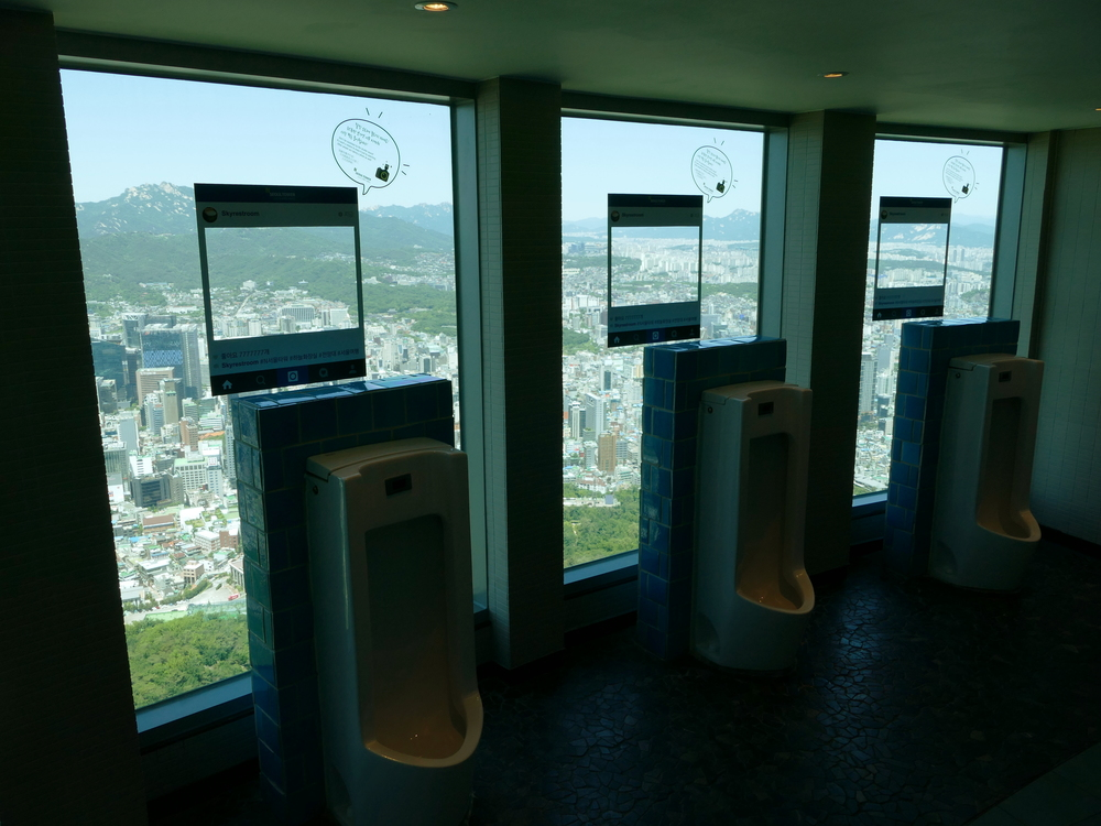 three urinals with big picture windows in front of them with one hell of a view of Seoul