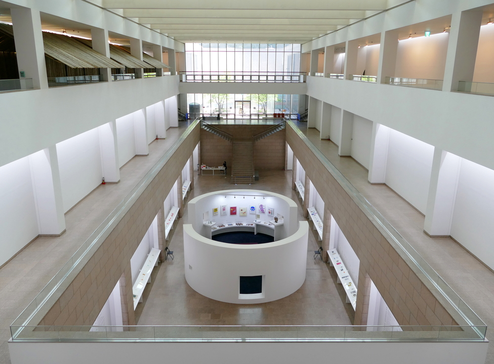a very symetrically composed photo of a white two storey gallery with a round semi-enclosed room in the centre of the first floor