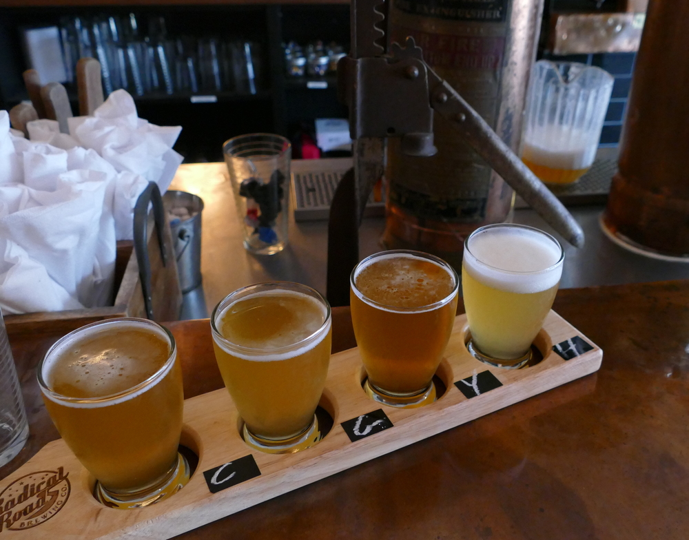 four sample-sized beers in a classic wood flight paddle
