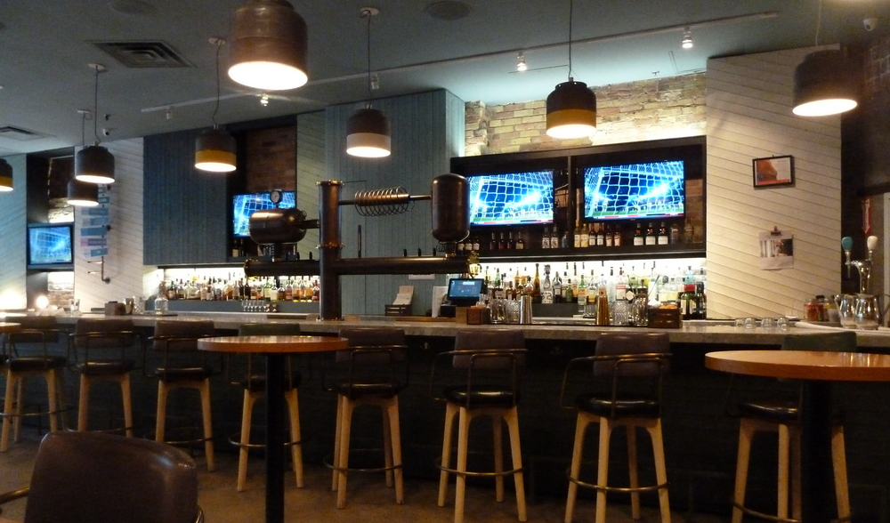 a bar with multiple TVs behind it and fancy beer-dispensing taps
