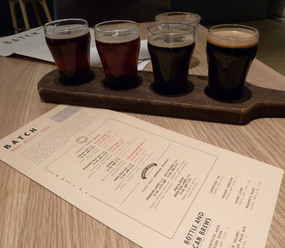 a flight of four beers and an difficult-to-read beer menu