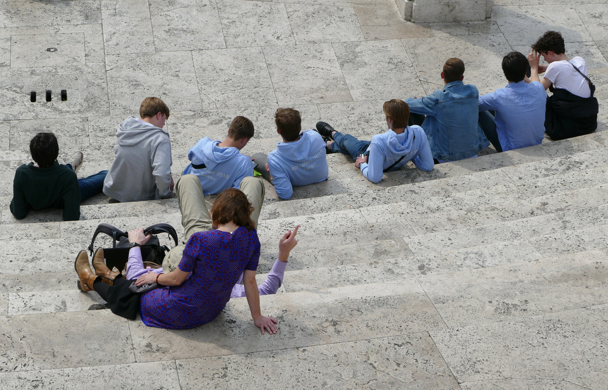 a group of people resting on the Spanish Steps, seen from above