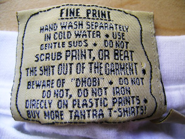 "t-shirt tag that says ""Do not scrub print, or beat the shit out of the garment"""