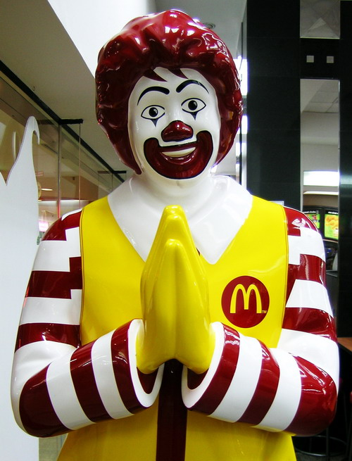 Ronald McDonald bowing namaste at the door of a McDonalds in Thailand