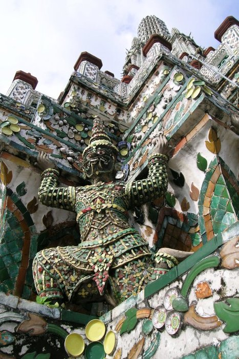 Demon sculpture holding up the towering pottery-plated Wat Arun