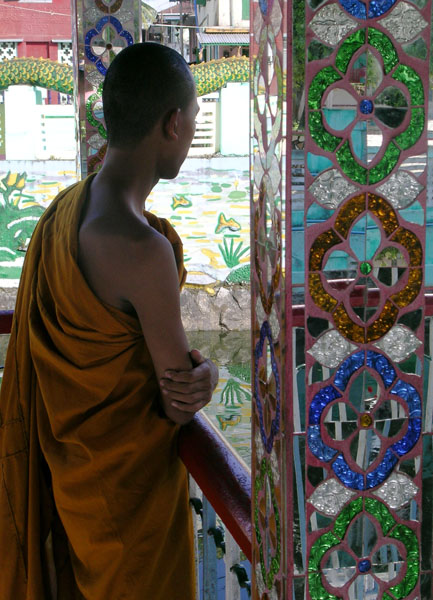 a Buddhist monk in an orange robe looking out between mirror-tiled columns