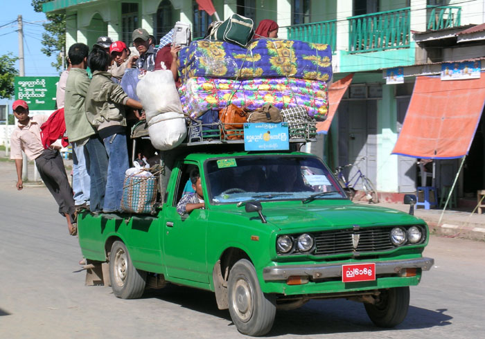 a small green pick-up truck with about 35 people and luggage on it