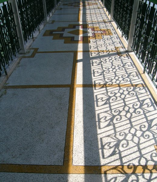 a tiled walkway with patterned shadows