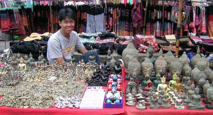 A vendor selling a large variety of brass Buddha images.