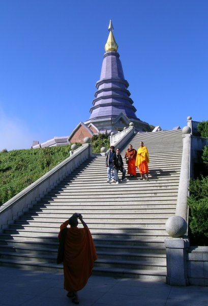 A monk with a digital camera takes a photo of two monks and two friends in front of a stupa.
