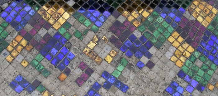 Colourful mirrored tile on concrete - a lot of the tiles have gone missing.