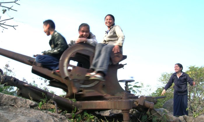 Kids riding on an old spinning Russian gun emplacement.