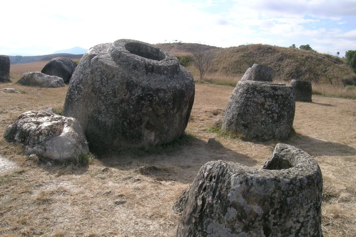 Several large stone jars on the dry grass hills.