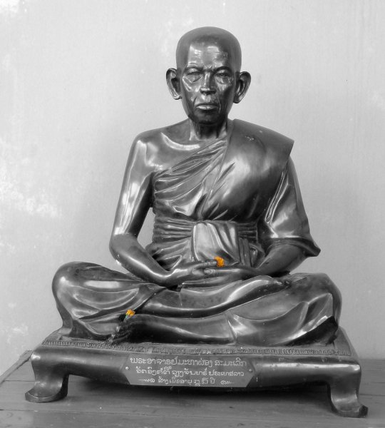 A sculpture of a monk sitting in half lotus with a couple small flowers placed on the sculpture.