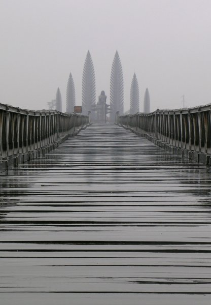 A long wood-planked bridge in the rain, with a menacing monument at the end.
