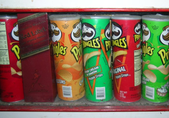 Several kinds of Pringles chips and a box of Johnnie Walker Red.