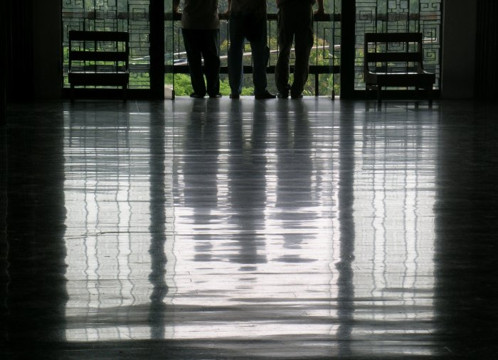 A floor reflection of three men standing in a window.