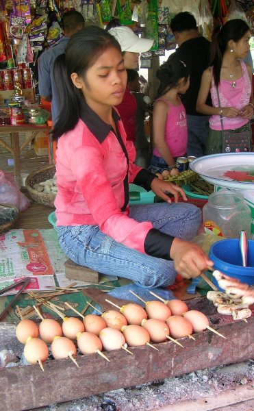 Vendor preparing eggs on a stick