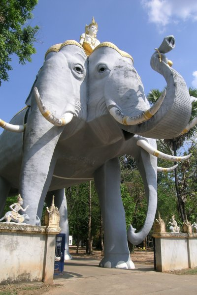 A massive three-headed elephant sculpture stands over the gate to a temple