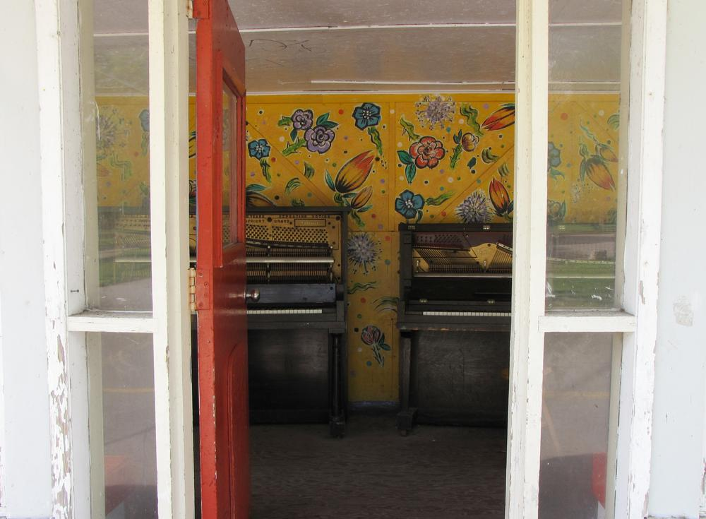looking through a door at two decrepit pianos