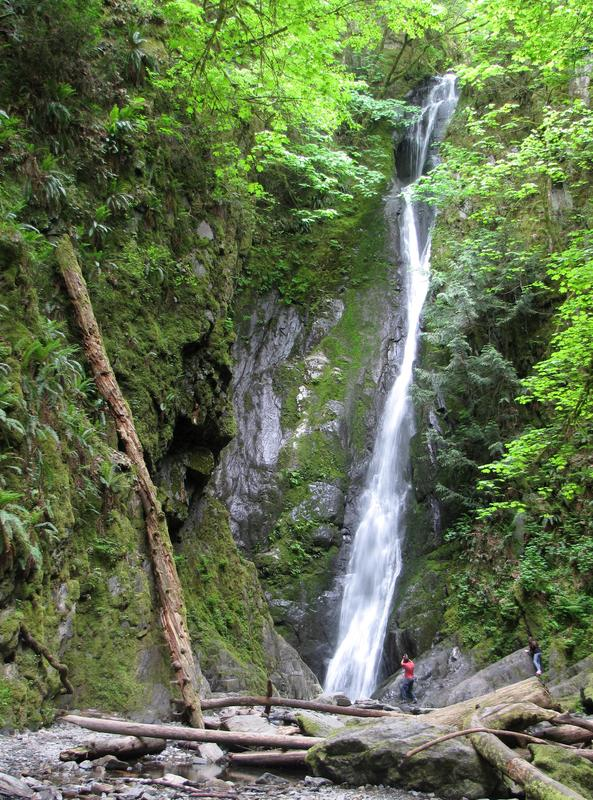 Very tall falls in Goldstream Provincial Park with a couple people in front of it.