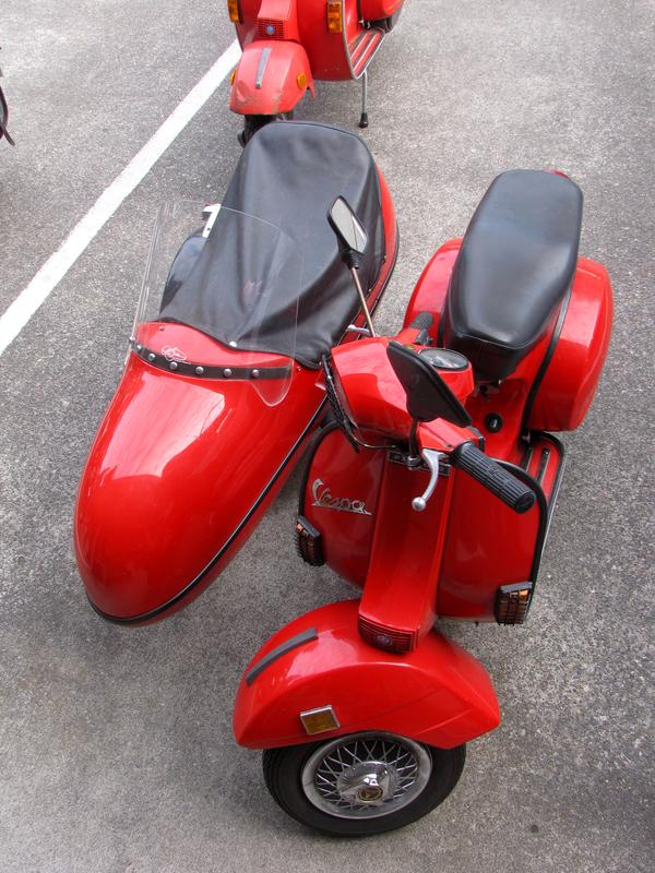 A bright red Vespa scooter with sidecar